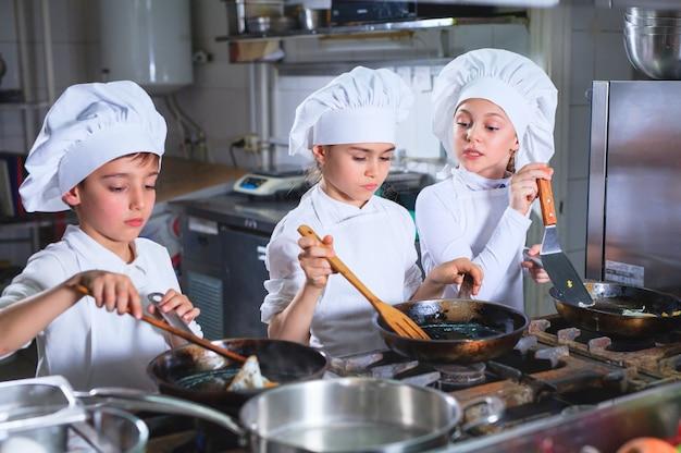 Kinder, die das mittagessen in einer restaurantküche kochen. Premium Fotos