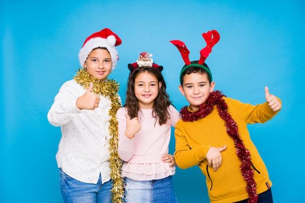 Kinder, die den weihnachtstag tut ausdrücke feiern Premium Fotos