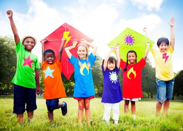 Kinder, die drachen-spielerisches freundschafts-konzept fliegen Premium Fotos