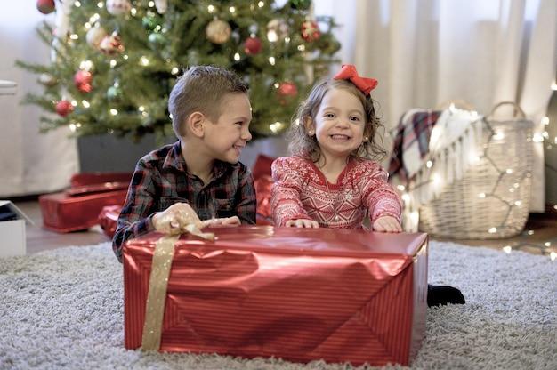 Kinder, die ein großes weihnachtsgeschenk in einem haus mit dem weihnachtsbaum halten Kostenlose Fotos