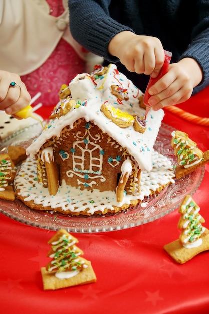 Kinder, die ein lebkuchenhaus verzieren Premium Fotos