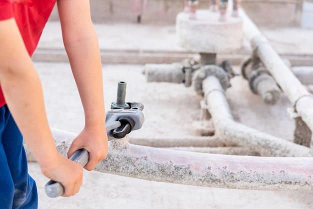 Kinder, die einen geraden hochleistungsrohr-sanitärschlüssel verwenden, um ein rohr zu reparieren. Premium Fotos