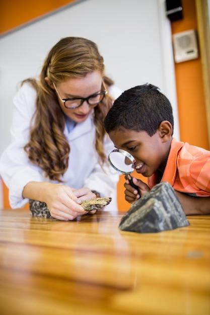 Kinder, die fossilien mit einer lupe schauen Premium Fotos