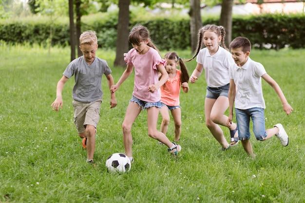 Kinder, die fußball auf gras spielen Kostenlose Fotos
