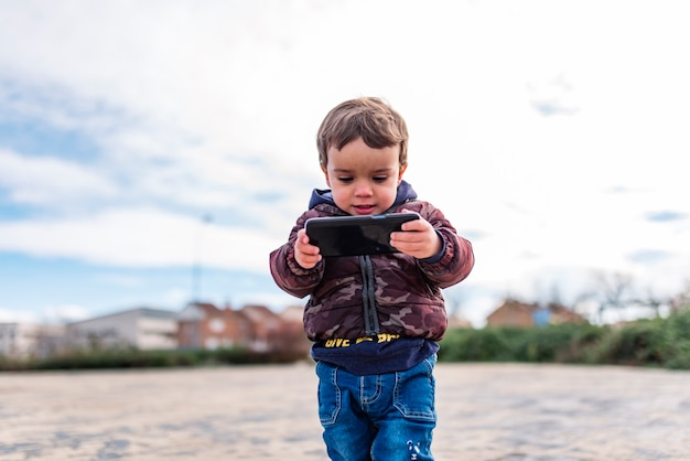 Kinder, die im freien mit einem mobiltelefon im internet surfen Premium Fotos