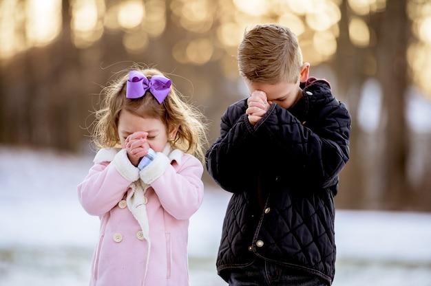 Kinder, die in einem garten beten, der im schnee mit einem verschwommenen hintergrund bedeckt ist Kostenlose Fotos