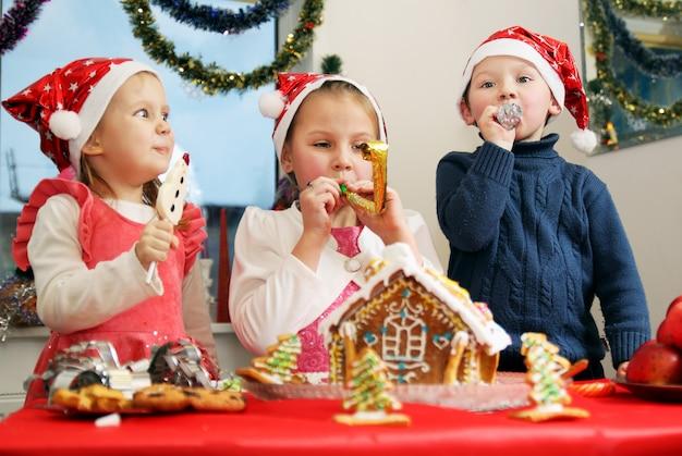 Kinder, die lebkuchenhaus verzieren Premium Fotos