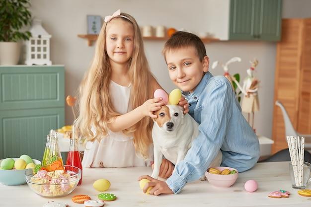 Kinder, die ostereier an der küche auf einem hund halten Premium Fotos
