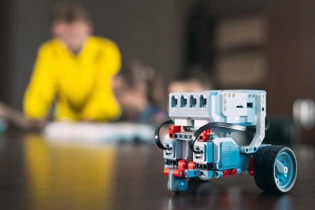 Kinder, die roboter mit lehrer herstellen. frühe entwicklung, diy, innovation, moderne technologie. Premium Fotos
