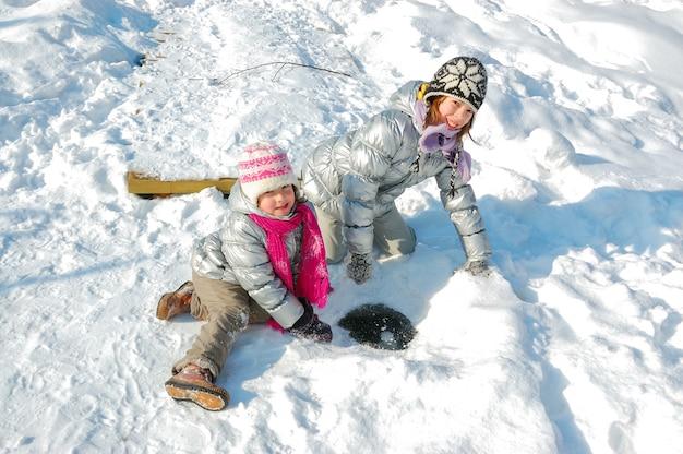 Kinder, die spaß im winter draußen haben, kinder, die mit schnee spielen Premium Fotos