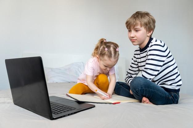 Kinder, die zu hause auf dem bett mit laptop lernen Premium Fotos