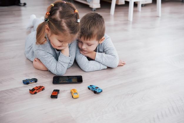 Kinder, die zu hause digitale geräte verwenden. bruder und schwester im schlafanzug schauen sich zeichentrickfilme an und spielen auf ihrem technologietablett Premium Fotos