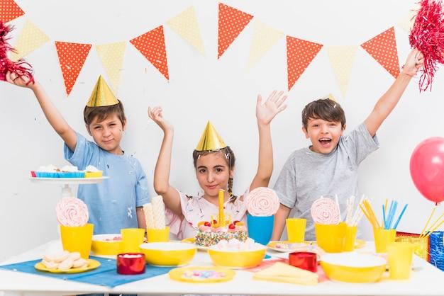 Kinder, die zu hause geburtstagsfeier mit vielzahl des lebensmittels auf tabelle feiern Kostenlose Fotos