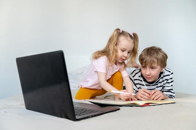 Kinder, die zu hause mit laptop und buch lernen Premium Fotos