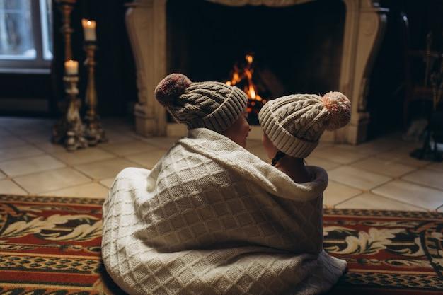 Kinder, die zusammen nahe kamin spielen, spaß in der winterzeit lächeln und haben. weihnachten, neues jahr, winterkonzept Premium Fotos