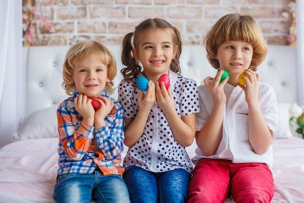Kinder, eine frau und zwei jungen halten ostereier in den händen. lustiges foto. entzückendes kind in farbigen kleidern, die urlaub genießen Premium Fotos
