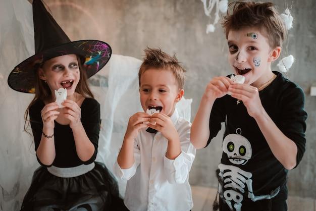 Kinder essen halloween-süßigkeiten auf einer kostümparty Premium Fotos