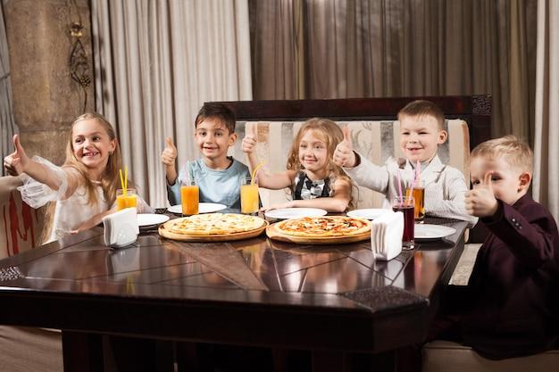 Kinder essen pizza in einem restaurant. Premium Fotos