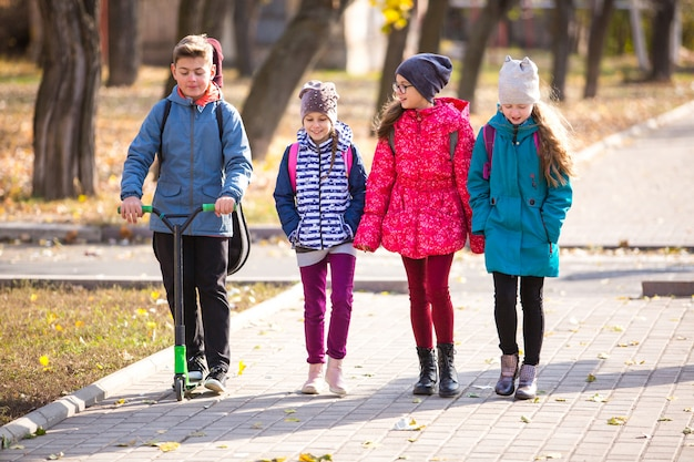 Kinder gehen mit einer lustigen gesellschaft auf dem bürgersteig zur schule. Premium Fotos