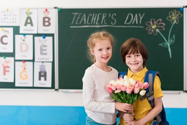 Kinder halten einen blumenstrauß für ihren lehrer zusammen Kostenlose Fotos