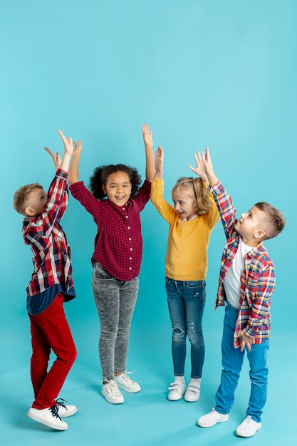 Kinder im kopierraum mit erhobenen händen Premium Fotos