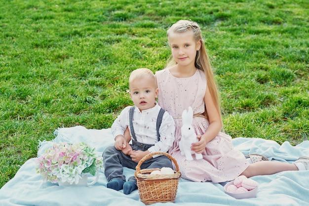 Kinder im park auf ostern picknick mit eiern und kaninchen Premium Fotos