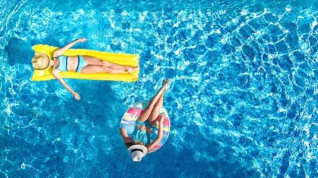 Kinder in der luftbrummenansicht des swimmingpools von oben, glückliche kinder schwimmen auf aufblasbarem ringkrapfen und matratze, aktive mädchen haben spaß im wasser auf familienurlaub auf ferienort Premium Fotos