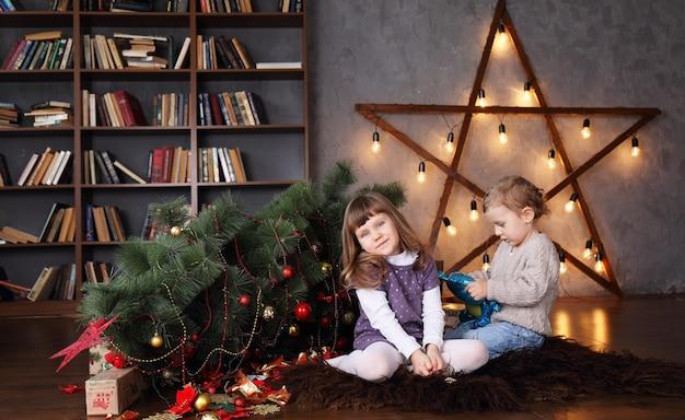 Kinder in der nähe eines umgestürzten weihnachtsbaumes Premium Fotos