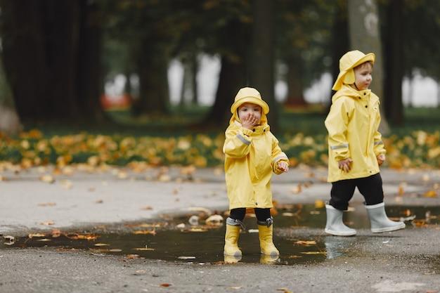 Kinder in einem herbstpark. kinder in gelben regenmänteln. leute, die spaß im freien haben. Kostenlose Fotos