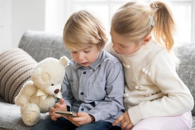 Kinder junge und mädchen, die den smartphone zusammen sitzen auf sofa verwendet Kostenlose Fotos