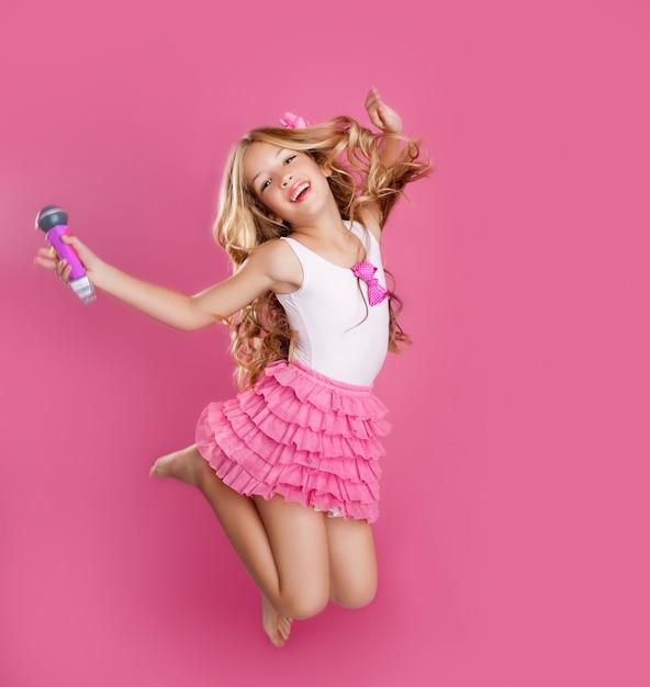 Kinder kleine starsängerin wie modepuppe mit mikrofon Premium Fotos