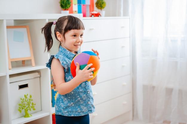 Kinder kleines mädchen spielen in einem kinderspielzimmer und werfen ball. konzept der interaktion eltern und kind Premium Fotos