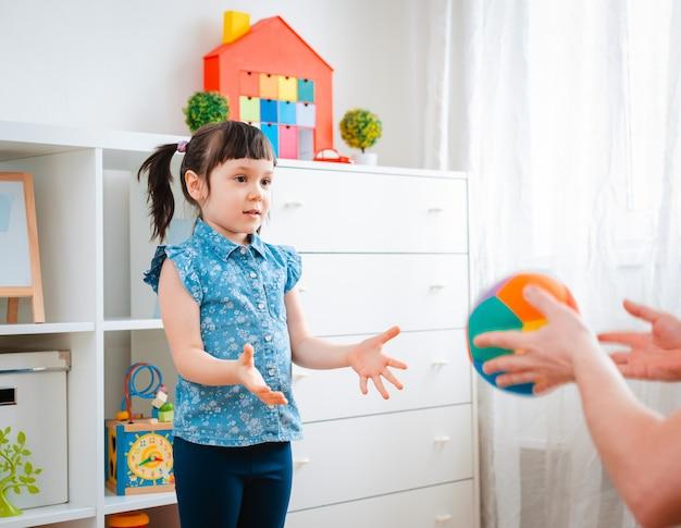 Kinder kleines mädchen spielen in einem kinderspielzimmer und werfen ball Premium Fotos
