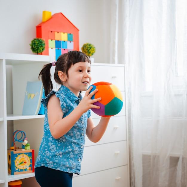 Kinder kleines mädchen spielen kinderspielzimmer, ball werfen. konzept interaktion eltern und kind Premium Fotos