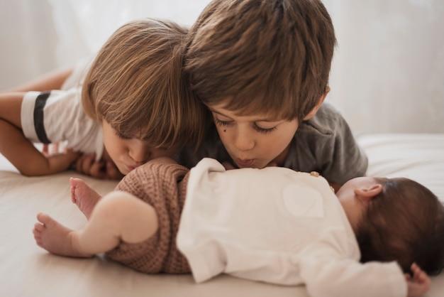 Kinder küssen ihren kleinen bruder Kostenlose Fotos