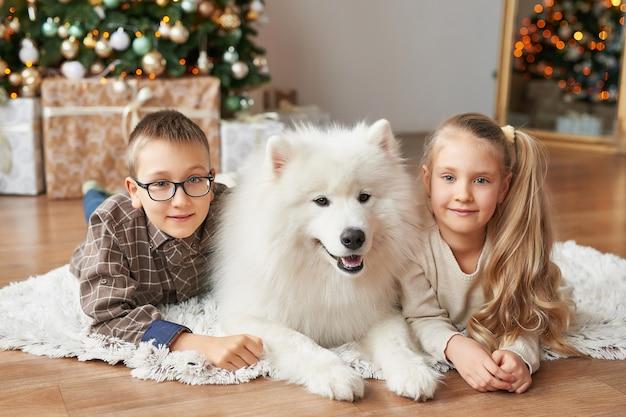 Kinder mädchen und jungen mit samojeden hund auf weihnachten hintergrund Premium Fotos