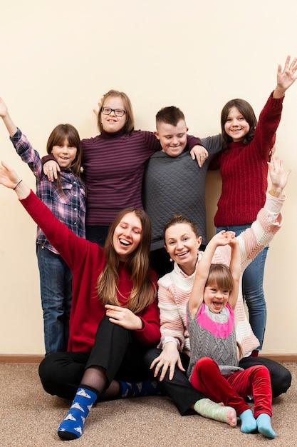Kinder mit down-syndrom und frau posieren glücklich Kostenlose Fotos