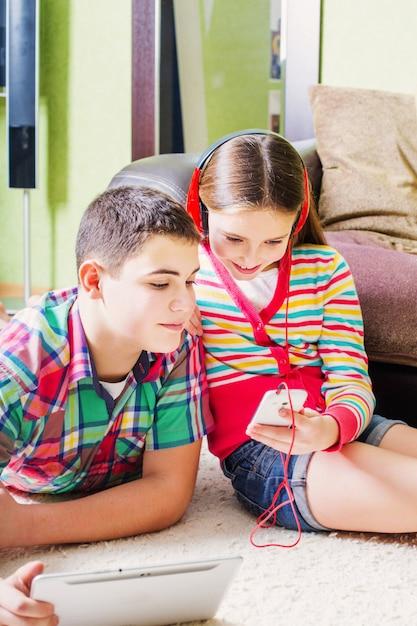 Kinder mit elektronischem tablet und handy Premium Fotos