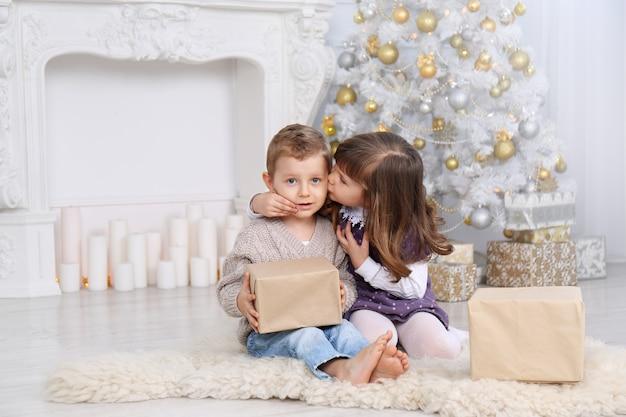 Kinder mit geschenken unter dem weihnachtsbaum Premium Fotos