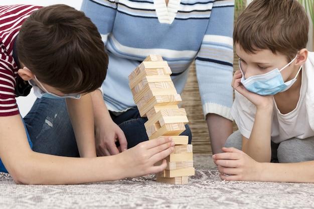 Kinder mit medizinischen masken spielen jenga mit mutter Kostenlose Fotos