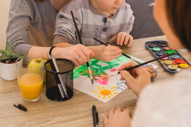 Kinder mit mutter malen bilder mit wasserfarbe und pinsel Premium Fotos