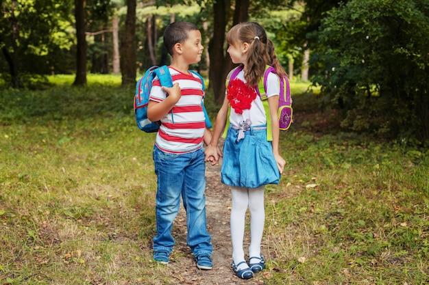 Kinder mit rucksäcken. jungen und mädchen sind freunde. zurück zur schule. das konzept der bildung, schule, Premium Fotos