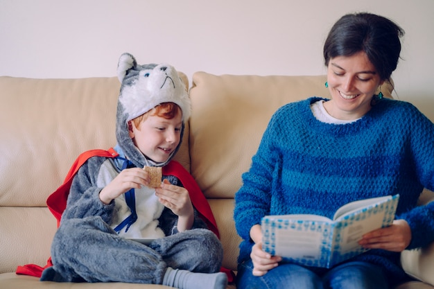 Kinder ohne schule verbringen ihre zeit drinnen zu hause. familienlebensstil drinnen. junge mutter liest ihren kindern in karnevalskostümen ein interessantes buch vor. geschichtenerzähler mit mama. Premium Fotos