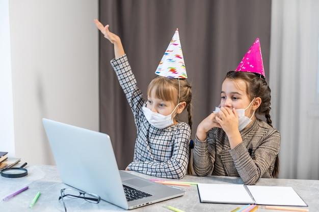 Kinder online-geburtstagsfeier. kleine mädchen in kleidern, hut feiern urlaub mit freunden. konferenz, videoanruf im laptop Premium Fotos