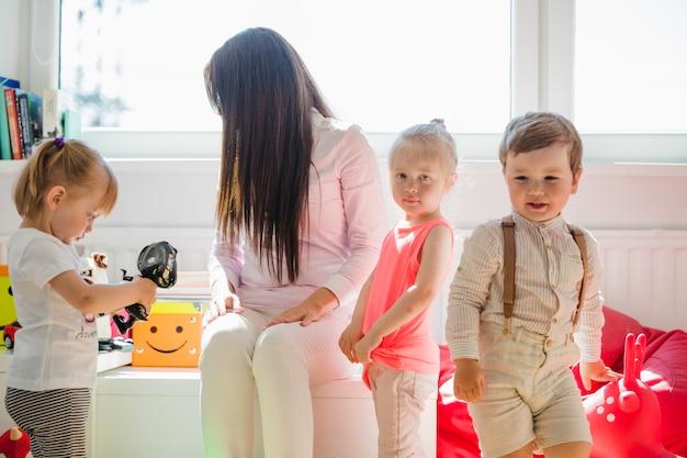Kinder posieren mit babysitter Kostenlose Fotos