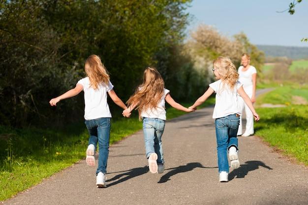 Kinder rennen einen pfad entlang, schwangere mutter steht Premium Fotos
