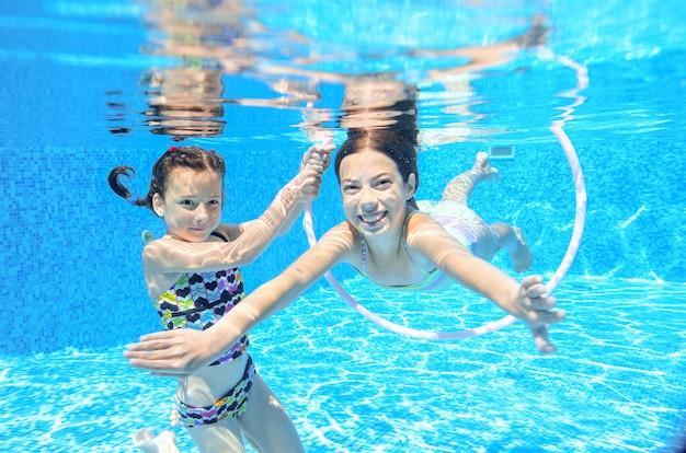 Kinder schwimmen im pool unter wasser, glückliche aktive mädchen haben spaß unter wasser, kindersport im familienurlaub Premium Fotos