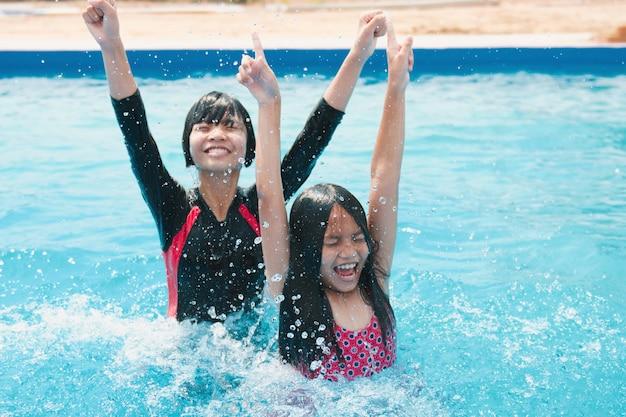 Kinder schwimmen und spielen im pool mit einem glücklichen lächeln Premium Fotos