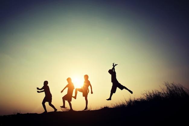 Kinder silhouetten spielen bei sonnenuntergang Kostenlose Fotos