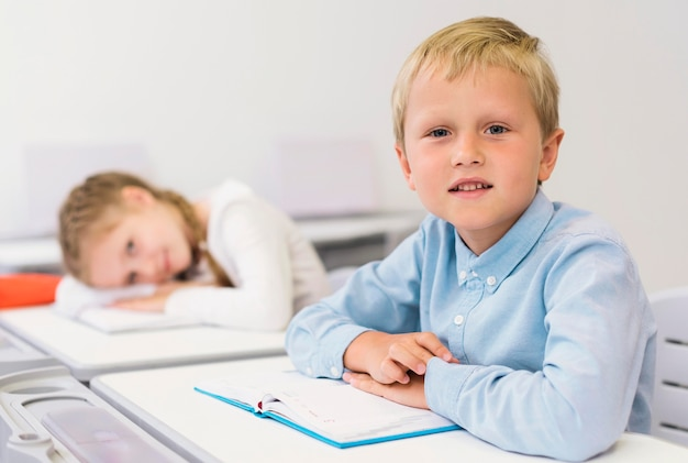 Kinder sitzen an ihrem schreibtisch im unterricht Kostenlose Fotos